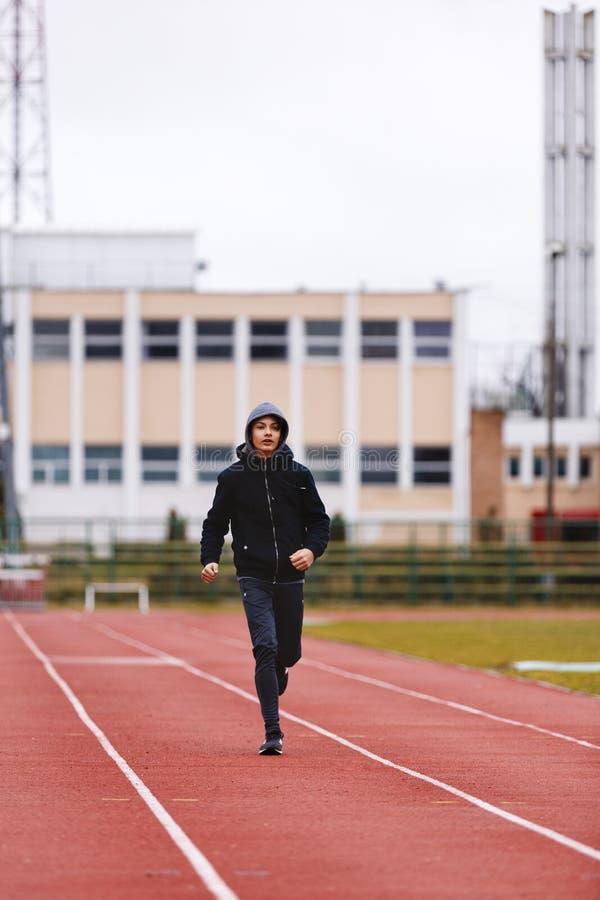 Spring idrottsman nenAsian för ung man på löparbana i stadion royaltyfria bilder