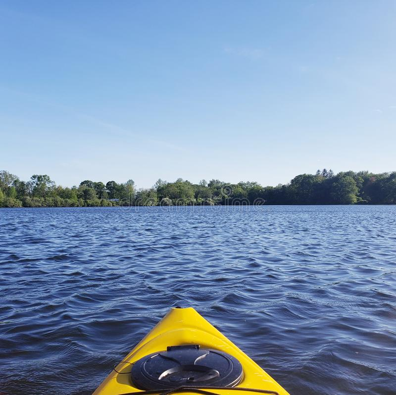 Spring Kayaking on a Peaceful Lake. What a great day to be out on the kayaks. Peaceful blue sky, new growth on the trees looking mighty lush contrasting with royalty free stock photography