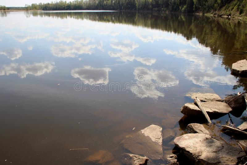 Spring landscape of the cloud pieces reflection in river stock photo