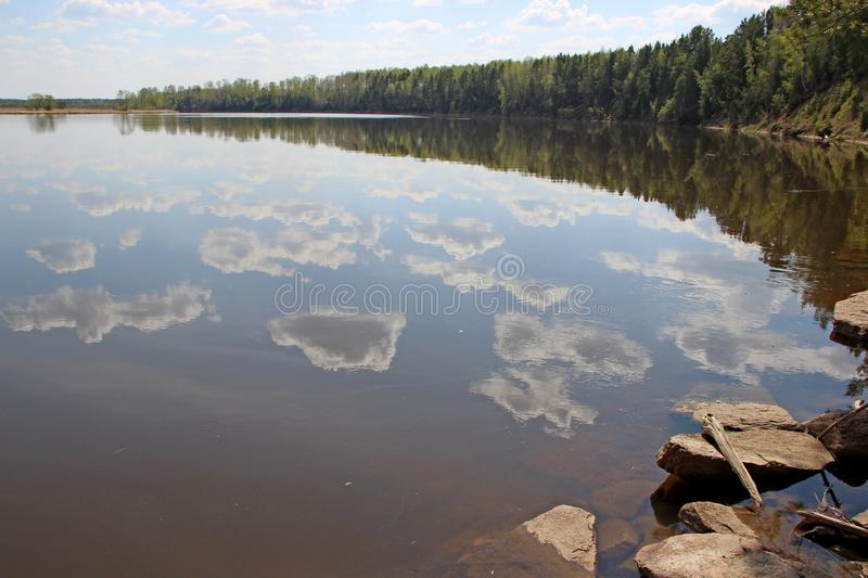 Spring landscape of the cloud pieces reflection in river stock image