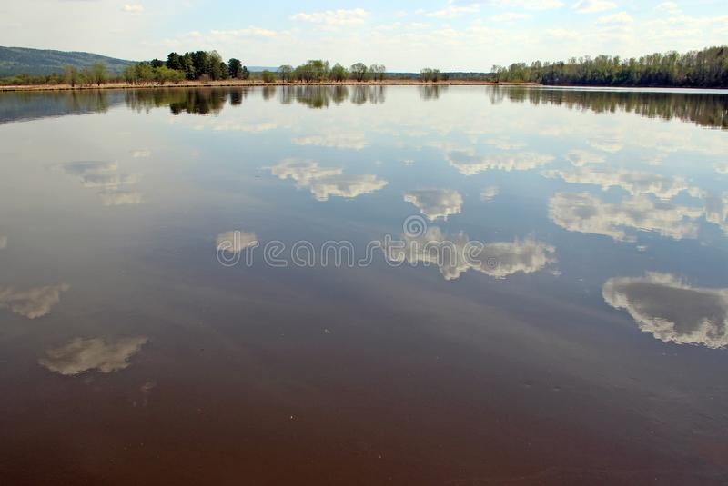 Spring landscape of the cloud pieces reflection in river royalty free stock photography