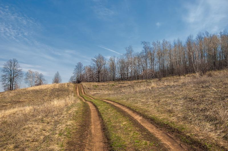 Spring landscape. country road on the spring field. hilly terrai royalty free stock photography