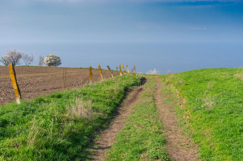 Landscape with an earth road  leading down to Kakhovka Reservoir riverside located on the Dnipro River near. Spring landscape with an earth road  leading down to stock image