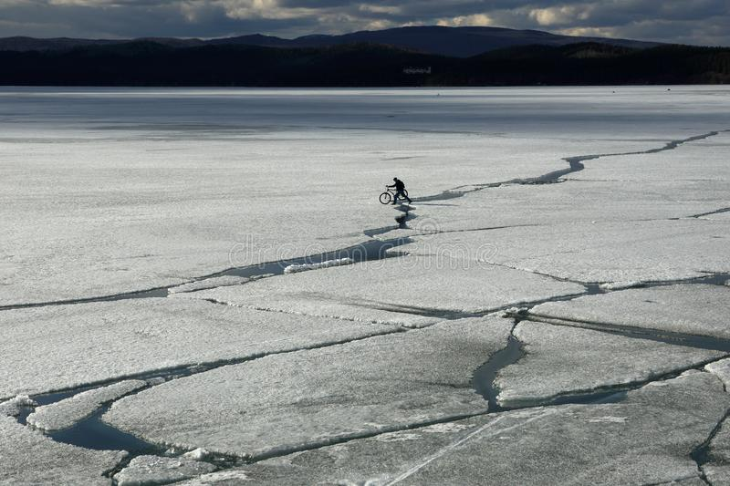 Spring landscape with ice drift on the lake and a cyclist riding on it stock photography