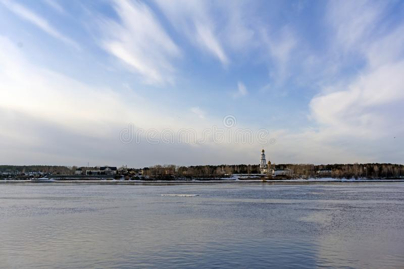 Spring landscape with an ice floe floating on the river and an Orthodox church on the far bank stock images