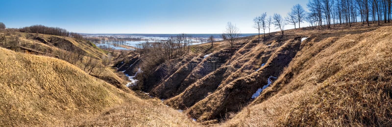 Spring landscape, panorama, banner - spurs of ravine near the flooding winding river over the meadows between hills and forests royalty free stock photo