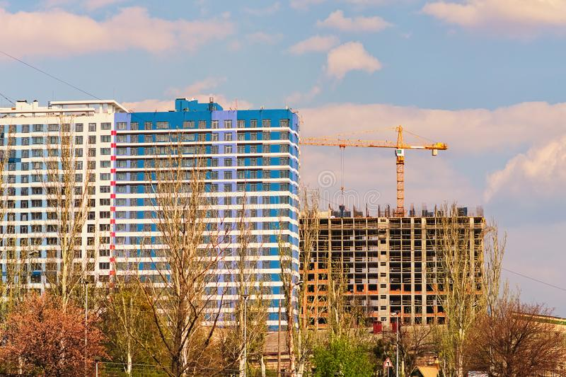 Spring landscape view of the process of building multistorey residential buildings. Building crane and building. Spring landscape view of the process of building stock photo
