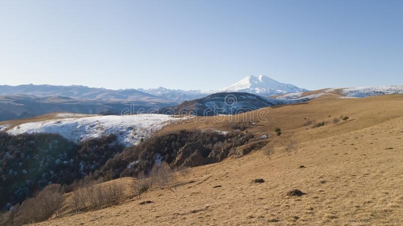 Spring landscape with views of a dry arid high-altitude field and mount Elbrus in the distance. Travel to Russia and the Caucasus royalty free stock photos