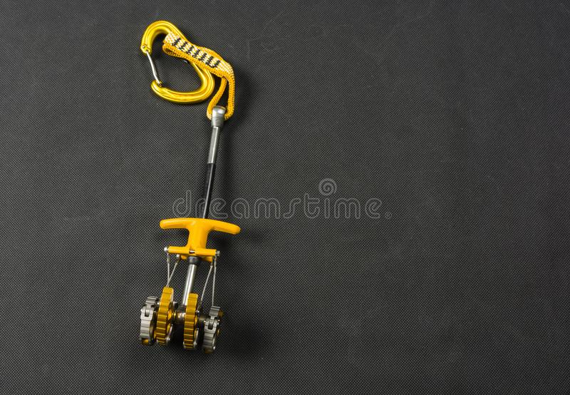 Spring-loaded camming device - a popular friend. Spring-loaded camming device in yellow with carabiner stock photos