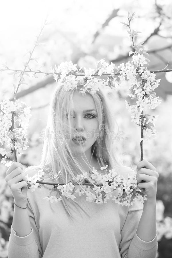 Spring make-up. Fashionable woman posing. woman holding frame of white, blossoming flowers stock photos