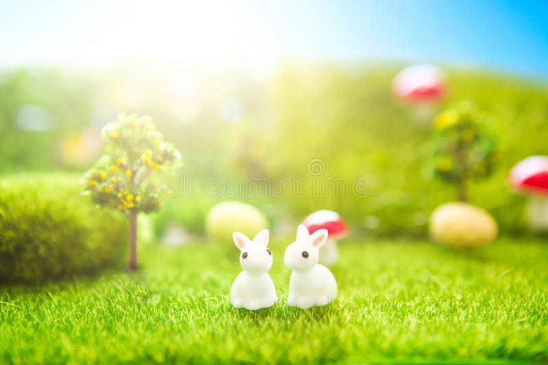Spring meadow with two white rabbit and easter eggs. Fairy tale stock photo