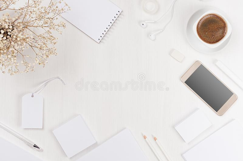Spring modern blank white business stationery set with copy space, card, label, paper, phone, coffee, flowers on white board. Spring modern blank white business stock image