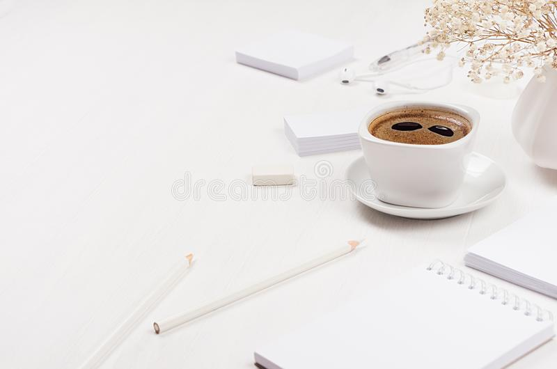 Spring modern simple work place of white office stationery set with coffee cup, flowers on soft light white wood table. Spring modern simple work place of white royalty free stock image