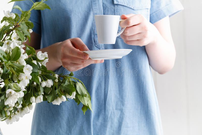 Spring morning, the girl drinks coffee with a bouquet of spring flowers in a vase royalty free stock photo