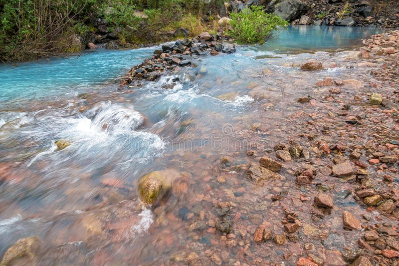Spring Mountains Water Beginning River. Blue spring in the mountains, source of crystal pure natural water; beginning of the river royalty free stock image