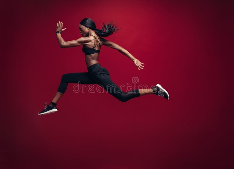 Spring och banhoppning för kvinnlig idrottsman nen arkivfoto