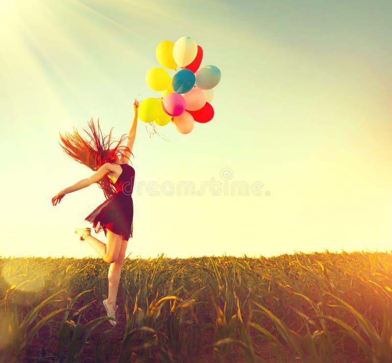 Spring och banhoppning för skönhetrödhårig manflicka på sommarfält med färgrika luftballonger arkivbilder