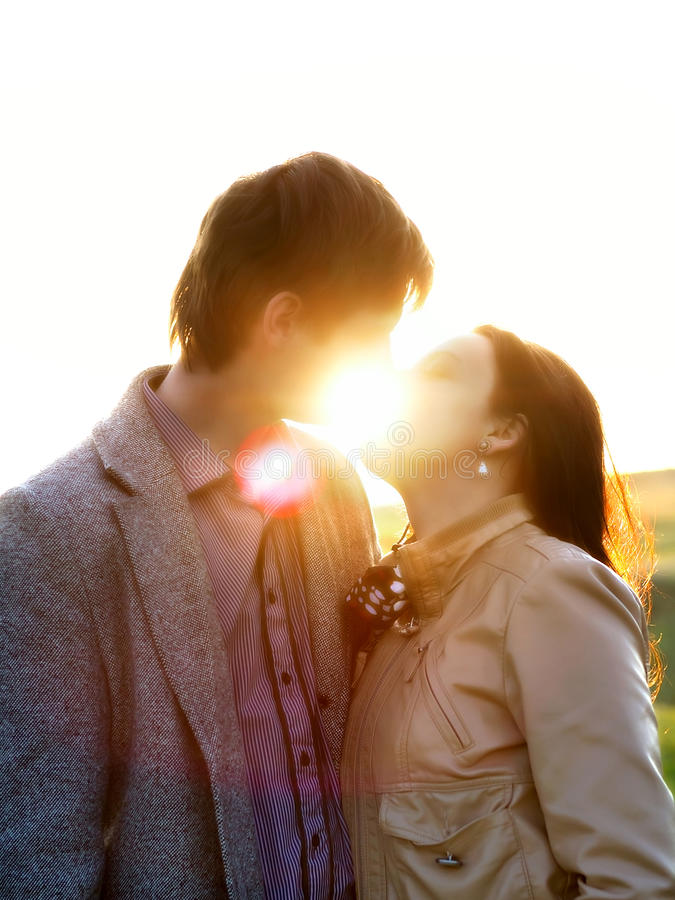 Spring outdoor portrait of a young couple kissing stock photography