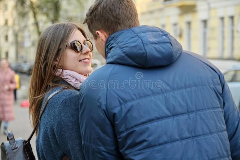 Spring outdoor portrait of young couple walking, happy attractive man and woman, city street background, back view stock photos