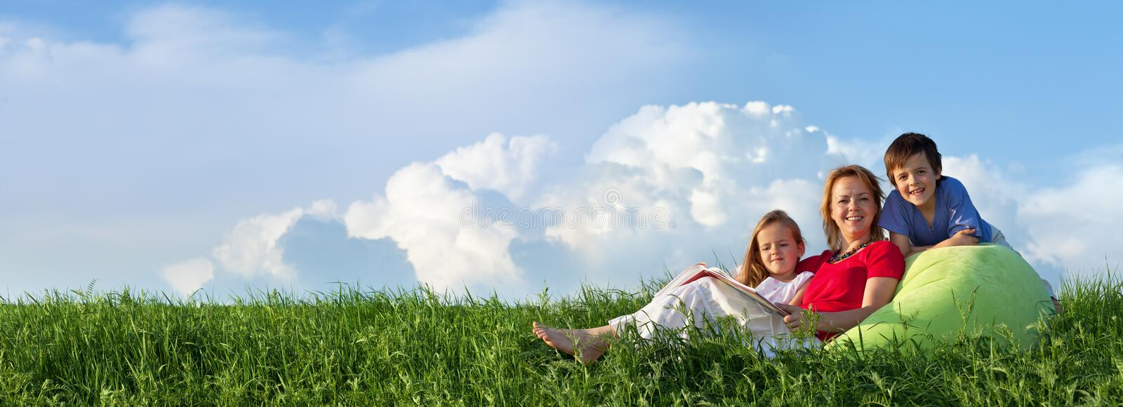 Spring panorama with family sitting outdoors royalty free stock images