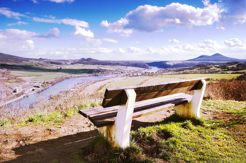 Spring photo of wooden bench on Doerellova vyhlidka view in Ceske stredohori in czech landscape with river Labe on background royalty free stock photos