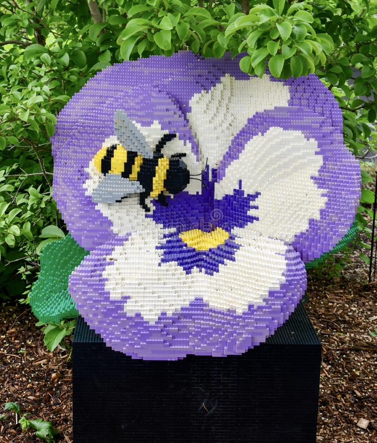 Violet Pansy and Bee. This is a Spring picture of a piece of public art titled: Violet Pansy and Bee; on exhibit at the Morton Arboretum in Lisle, Illinois in royalty free stock photography