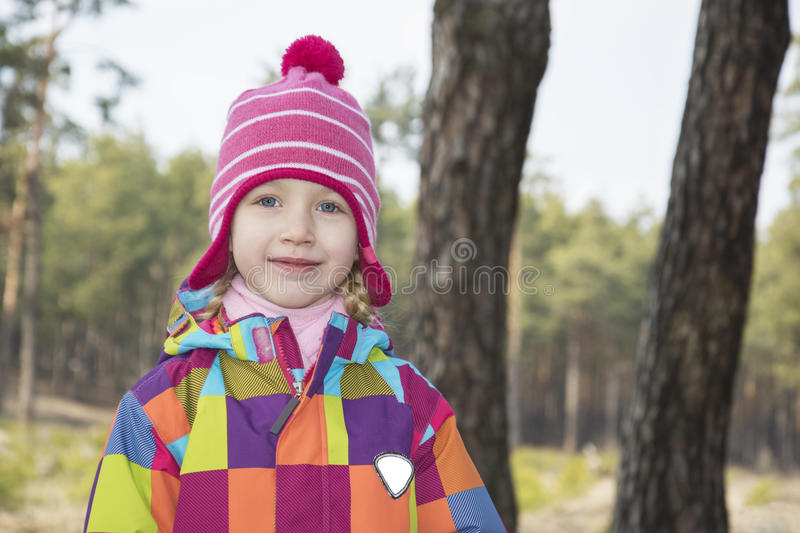 Spring in a pine forest girl sitting on driftwood. Spring in a pine forest blue-eyed girl is sitting on driftwood royalty free stock photo