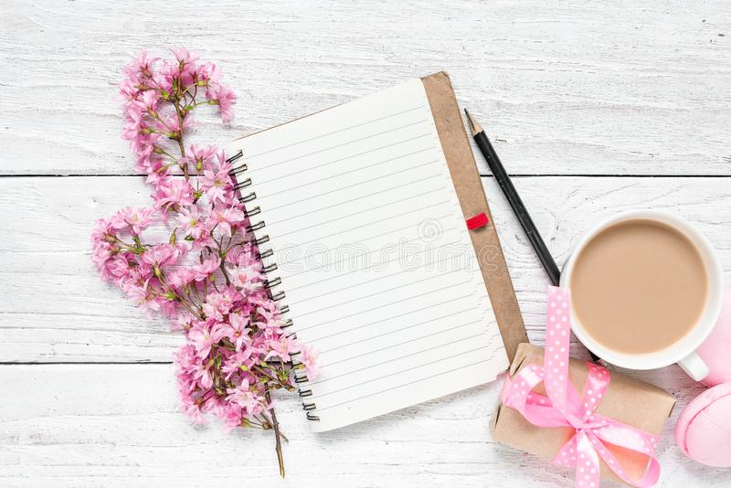 Spring pink blossoming flowers with blank paper notepad, macarons, coffee cup and gift box on white wooden table stock photo