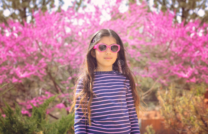 Spring pink blossoms. Pretty girl front of a tree with lots of pink blossoms royalty free stock photos