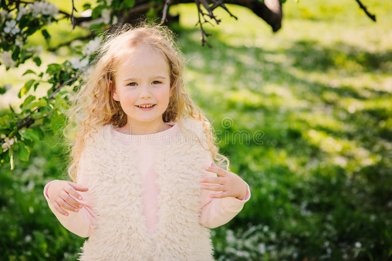 Spring portrait of beautiful dreamy curly 5 years old child girl. Walking in blooming garden royalty free stock photos