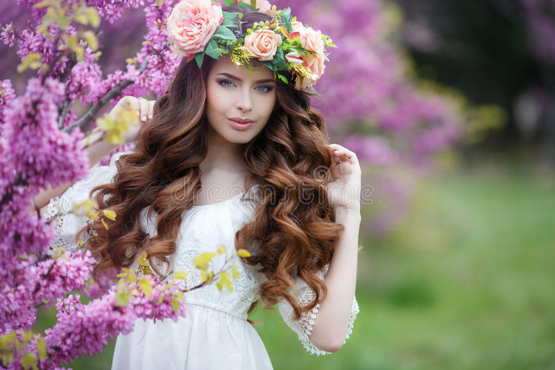 Spring portrait of a beautiful woman in a wreath of flowers. Long curly hair red color , gray eyes , light make-up and beautiful smile , wearing a white stock images