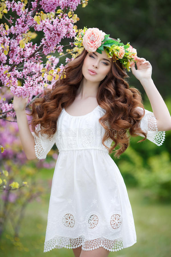 Spring portrait of a beautiful woman in a wreath of flowers. Long curly hair red color , gray eyes , light make-up and beautiful smile , wearing a white stock photos