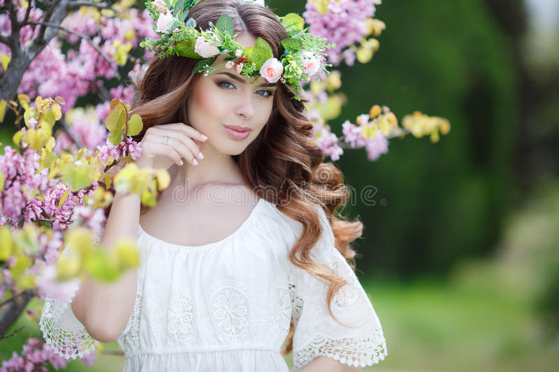 Spring portrait of a beautiful woman in a wreath of flowers. Long curly hair red color , gray eyes , light make-up and beautiful smile , wearing a white stock image