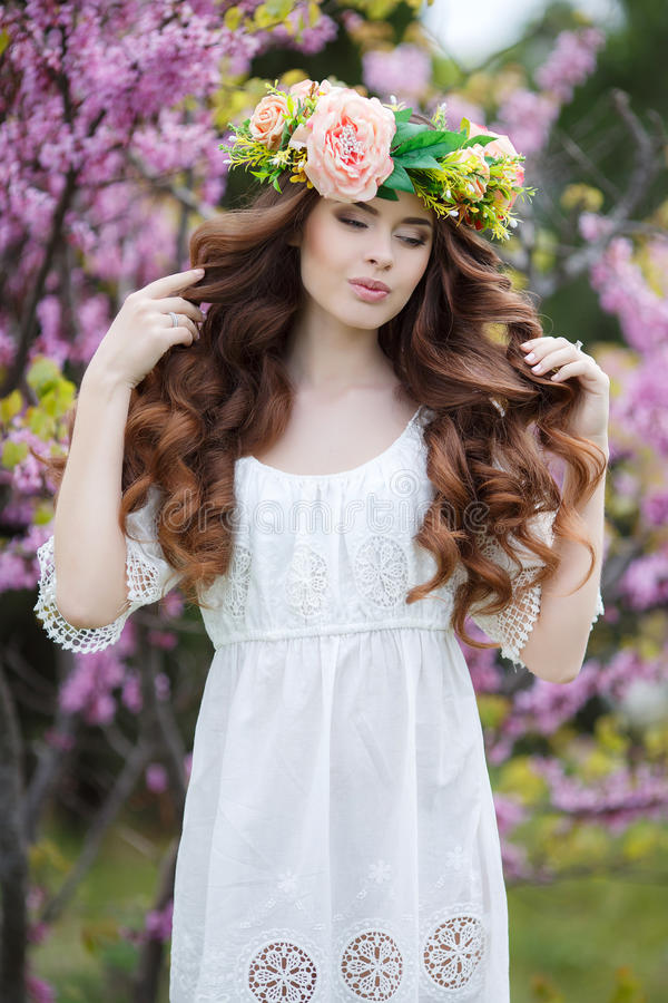 Spring portrait of a beautiful woman in a wreath of flowers. Long curly hair red color , gray eyes , light make-up and beautiful smile , wearing a white royalty free stock image