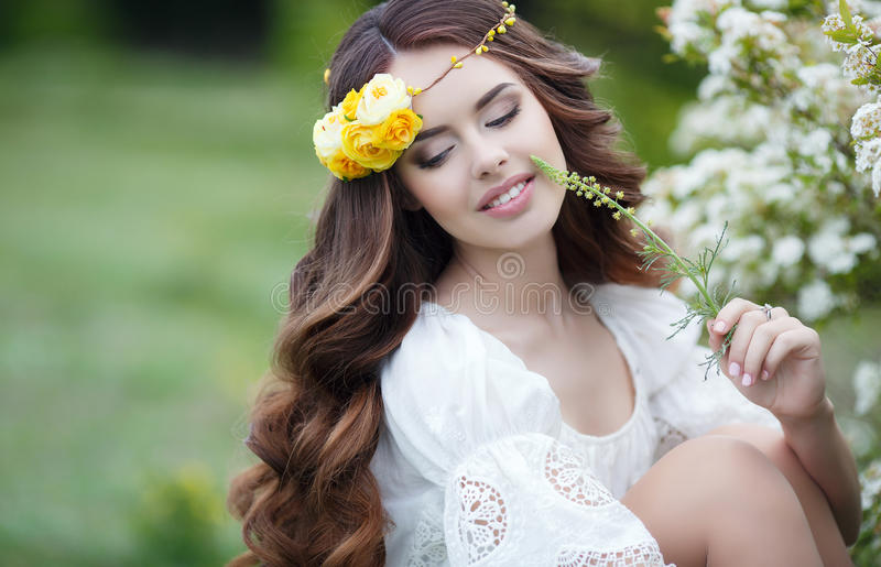 Spring portrait of a beautiful woman in a wreath of flowers. Long curly red hair,gray eyes,light makeup and a beautiful smile,dressed in a white summer dress royalty free stock photography