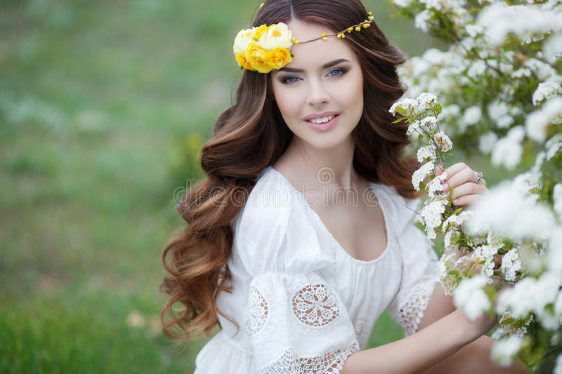 Spring portrait of a beautiful woman in a wreath of flowers. Long curly red hair,gray eyes,light makeup and a beautiful smile,dressed in a white summer dress royalty free stock image