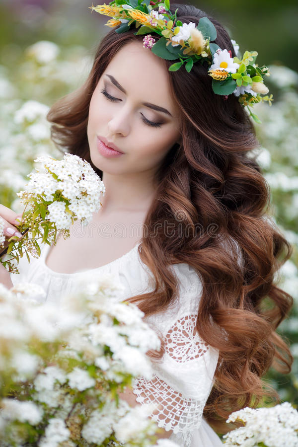 Spring portrait of a beautiful woman in a wreath of flowers. Long curly red hair,gray eyes,light makeup and a beautiful smile,dressed in a white summer dress stock photo