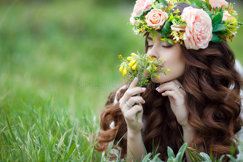 Spring portrait of a beautiful woman in a wreath of flowers. Long curly red hair,gray eyes,light makeup and a beautiful smile,dressed in a white summer dress royalty free stock images