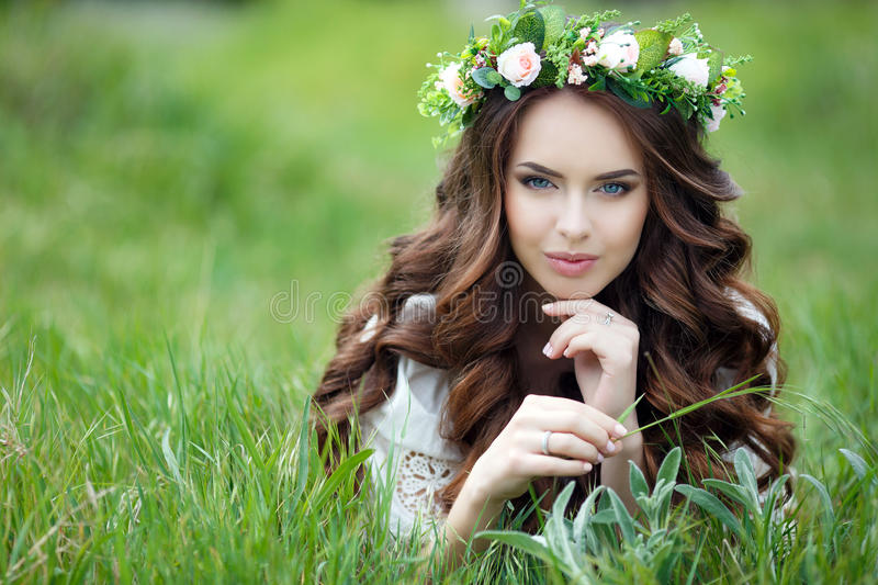 Spring portrait of a beautiful woman in a wreath of flowers. Long curly red hair,gray eyes,light makeup and a beautiful smile,dressed in a white summer dress royalty free stock photos