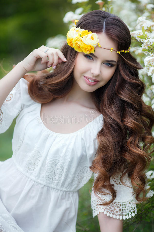 Spring portrait of a beautiful woman in a wreath of flowers. Long curly red hair,gray eyes,light makeup and a beautiful smile,dressed in a white summer dress stock photos