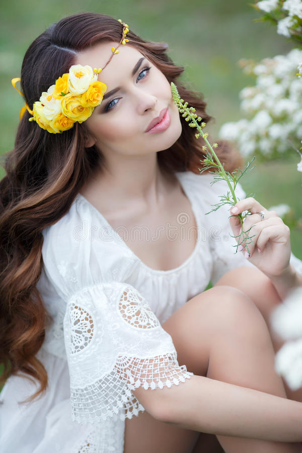 Spring portrait of a beautiful woman in a wreath of flowers. Long curly red hair,gray eyes,light makeup and a beautiful smile,dressed in a white summer dress stock images