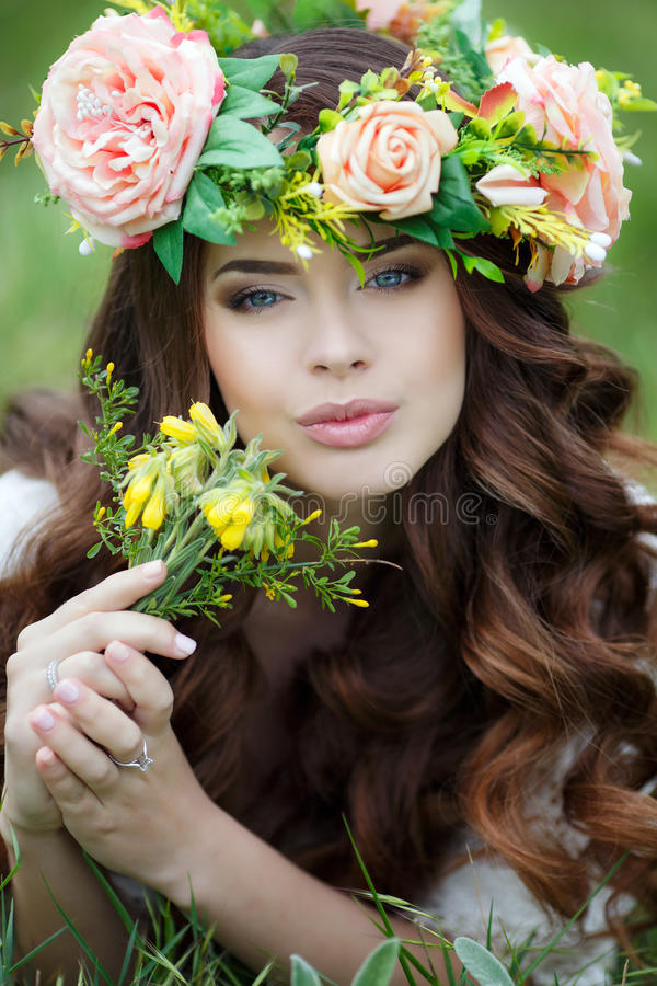 Spring portrait of a beautiful woman in a wreath of flowers. Long curly red hair, gray eyes, light makeup and a beautiful smile, dressed in a white summer stock image