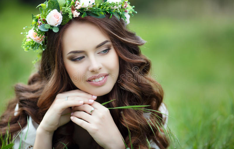 Spring portrait of a beautiful woman in a wreath of flowers. Long curly red hair,gray eyes,light makeup and a beautiful smile,dressed in a white summer dress stock image