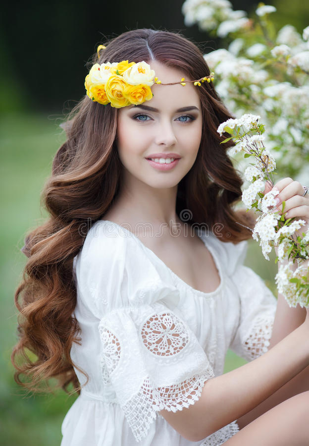 Spring portrait of a beautiful woman in a wreath of flowers. Long curly red hair,gray eyes,light makeup and a beautiful smile,dressed in a white summer dress royalty free stock photo