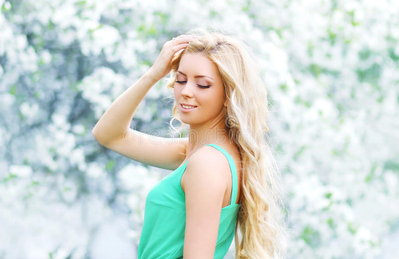 Spring portrait of beautiful young woman enjoying in a flowering stock image