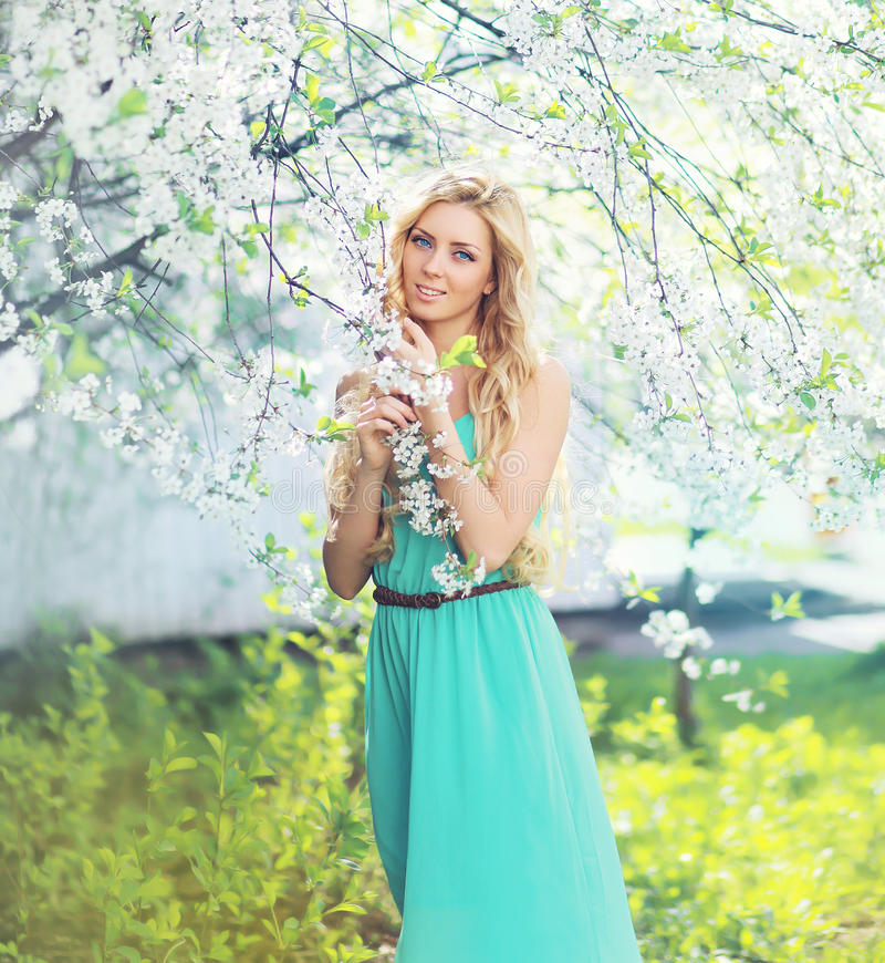Spring portrait of a beautiful young woman enjoying smell petals stock images