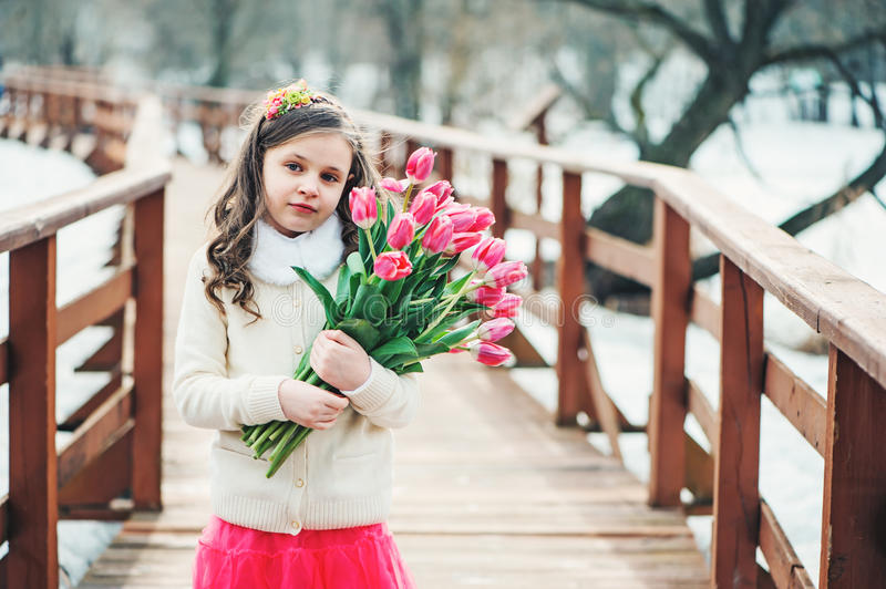 Spring portrait of child girl with tulips bouquet on the walk stock images