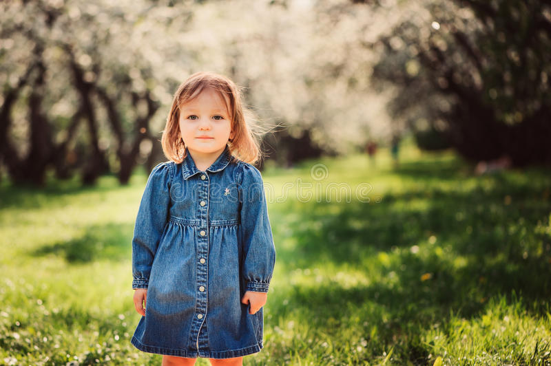 Spring portrait of cute little toddler girl in blue jeans dress walking in blooming park royalty free stock images