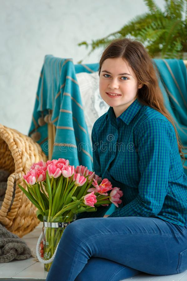 Spring portrait of a girl with pink tulips stock image