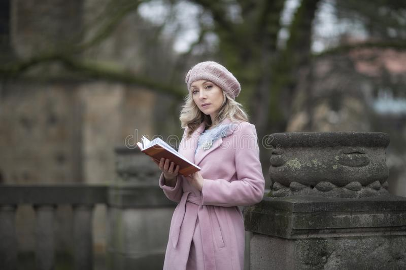 Spring portrait of a girl reading a book in the Park.Female portrait.Blonde in pink stock photos